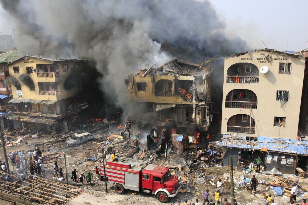 Description of . A fire truck passes a warehouse on fire on Lagos Island in Lagos, Nigeria, on Wednesday, Dec. 26, 2012. An explosion ripped through a warehouse Wednesday where witnesses say fireworks were  stored in Nigeria\'s largest city, sparking a fire. It wasn\'t immediately clear if anyone was injured in the blast that firefighters and locals struggled to contain. (AP Photo/Jon Gambrell)
