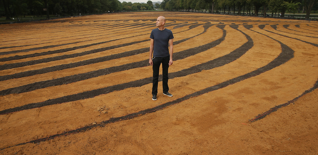 . Cuban-American artist Jorge Rodriguez-Gerada poses for photographs while standing in his six-acre sand and soil \'facescape\' on the JFK Hockey Field along the north side of the Reflecting Pool on the National Mall October 1, 2014 in Washington, DC.  (Photo by Chip Somodevilla/Getty Images)