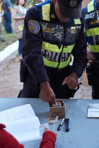 Election day in Santa Ana: <br /> A policeman puts his thumb in the indelible ink jar.