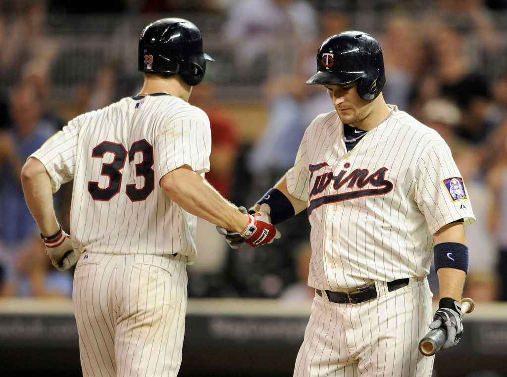 . Josh Willingham #16 of the Minnesota Twins congratulates teammate Justin Morneau #33 on a solo home run against the Kansas City Royals during the ninth inning. (Photo by Hannah Foslien/Getty Images)