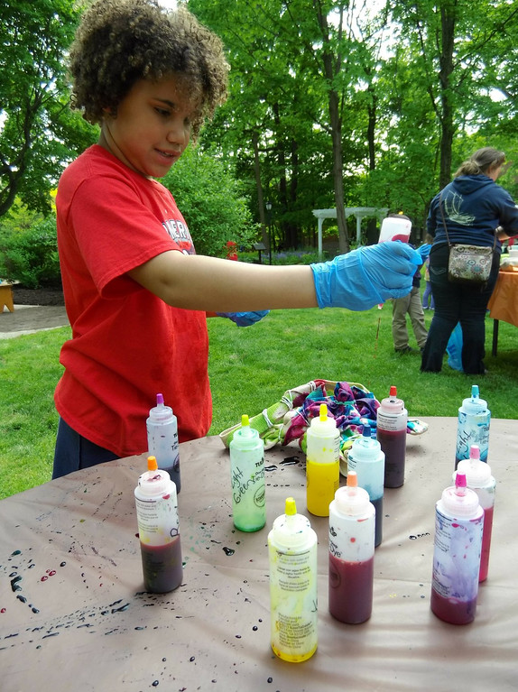 . Kyra Haffa drizzles on the dye whiel tie-dyeing her craft bag. (Courtesy Mentor Public Library)