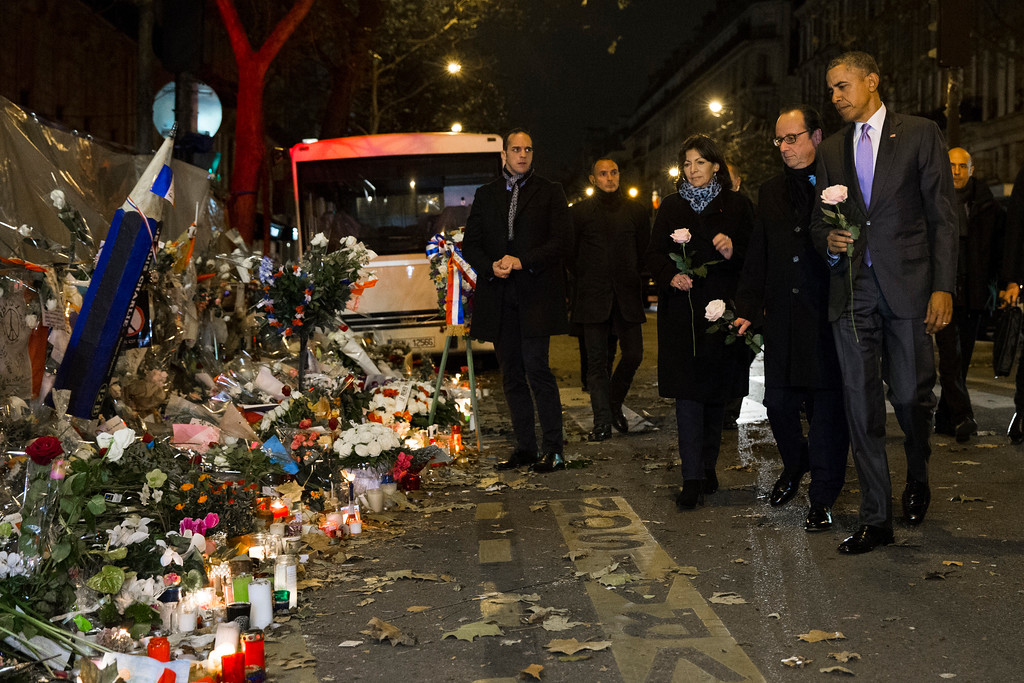 . President Barack Obama, right, French President Francois Hollande, second from right, and Paris Mayor Anne Hidalgo arrive at the Bataclan, site of one of the Paris terrorists attacks, to pay their respects to the victims, after Obama arrived in town for the COP21 climate change conference, on Monday, Nov. 30, 2015, in Paris. (AP Photo/Evan Vucci)
