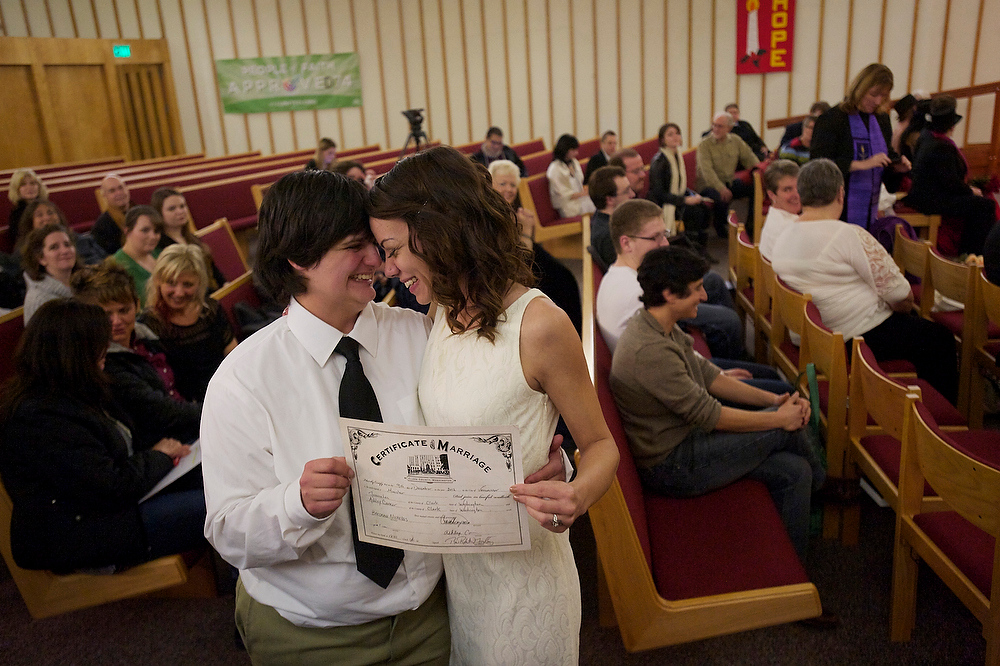 . Jessica Lee, 19, left, and Ashley Cavner, 21, from Vancouver, Washington, completed their wedding vows shortly after midnight Sunday morning Dec. 9, 2012 in Clark County. Sunday is the first day same-sex couples can marry under Washington state\'s new voter-approved law allowing gay marriage. Minister Rob Figley presided over the wedding at the First Congregational Church in Vancouver, WA. (AP Photo/Steven Lane, The Columbian)