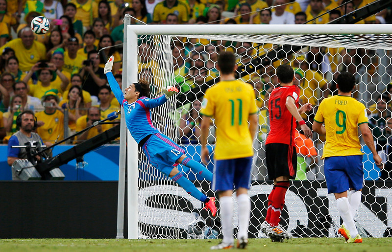. Mexico\'s goalkeeper Guillermo Ochoam, left, dives at a wide shot on the goal during the group A World Cup soccer match between Brazil and Mexico at the Arena Castelao in Fortaleza, Brazil, Tuesday, June 17, 2014.  (AP Photo/Eduardo Verdugo)