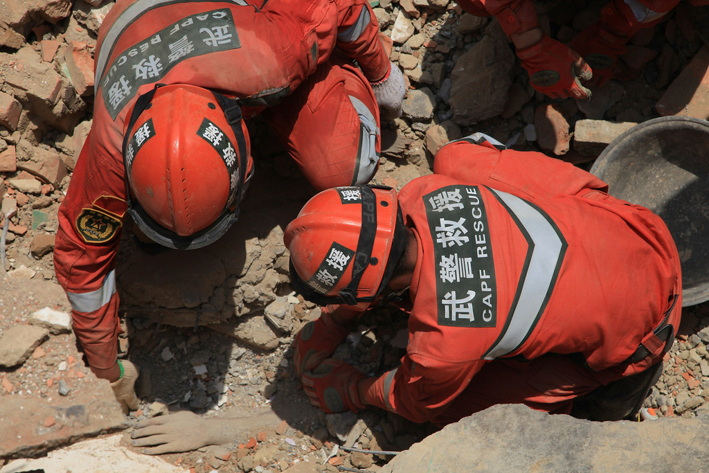 . Rescuers dig out the body of an earthquake victim buried in debris at Longtoushan township of Ludian county in Zhaotong, southwest China\'s Yunnan province, on August 5, 2014.   AFP PHOTOSTR/AFP/Getty Images