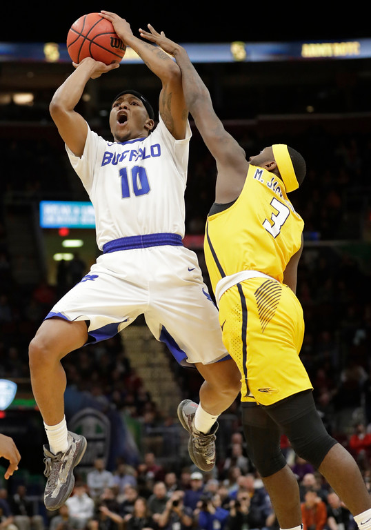 . Buffalo\'s Wes Clark (10) is fouled by Toledo\'s Marreon Jackson (3) during the second half of an NCAA college basketball championship game of the Mid-American Conference tournament, Saturday, March 10, 2018, in Cleveland. Buffalo won 76-66. (AP Photo/Tony Dejak)