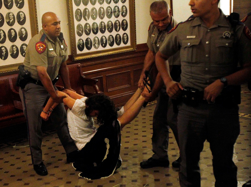 . An abortion rights activist is handcuffed after being removed from the Senate gallery after disrupting the Senate\'s special session to consider legislation restricting abortion rights in Austin, Texas July 12, 2013. The Republican proposal that would ban most abortions in Texas after 20 weeks of pregnancy moved toward a possible final vote in the state Senate Friday, and Democrats fiercely opposed to the measure conceded they will not be able to stop it. Davis drew national attention last month by staging a filibuster on the final day of a special session.  REUTERS/Mike Stone