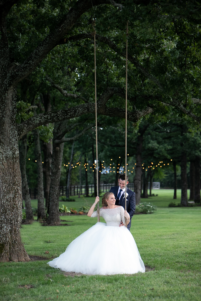 a groom pushing his bride on a tree swing minutes after their wedding