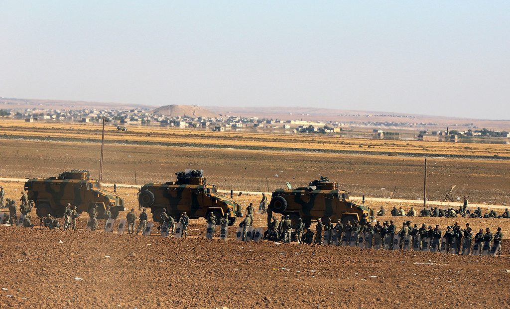 . Turkish soldiers line up as several hundred Syrian refugees wait to cross into Turkey at the border in Suruc, Turkey, Sunday, Sept. 21, 2014. (AP Photo/Burhan Ozbilici)