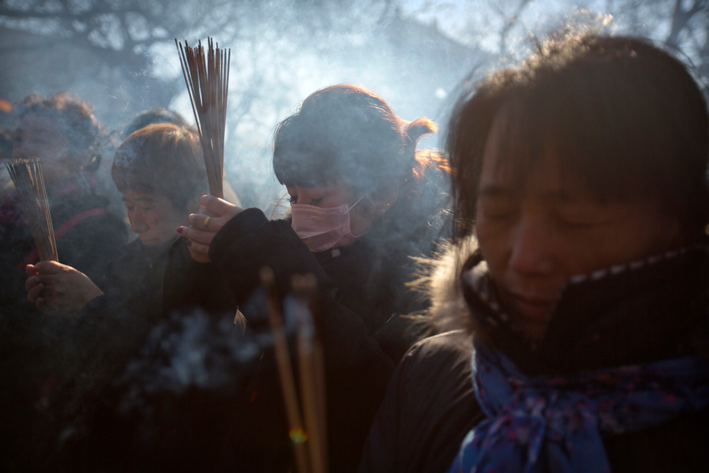 . People pray on the first day of the Lunar New Year at the Lama Temple in Beijing, Friday, Feb. 16, 2018.  (AP Photo/Mark Schiefelbein)