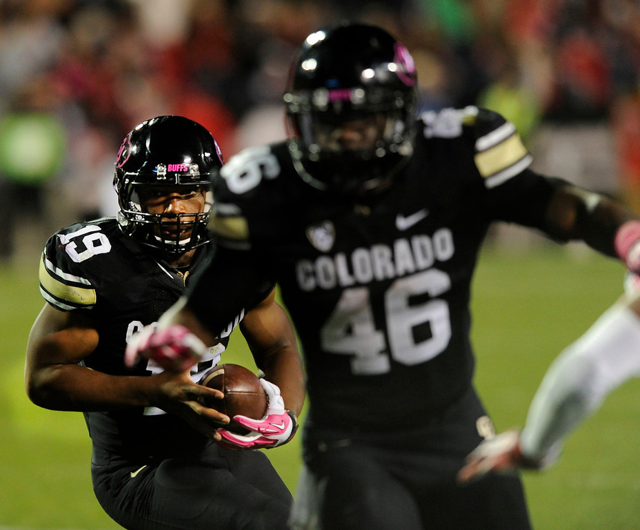 . BOULDER, CO. - OCTOBER 26: Colorado tail back Michael Adkins II (19) followed blocker Christian Powell (460 on a run in the second half. The University of Colorado football team hosted Arizona Saturday night, October 26, 2013. Photo By Karl Gehring/The Denver Post