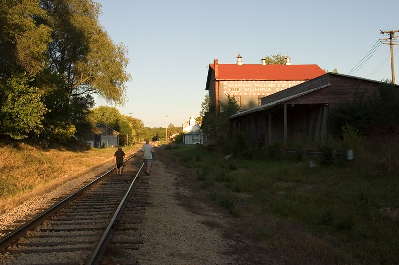 Two boys walking on railroad track. Palmyra, Wisconsin, USA.