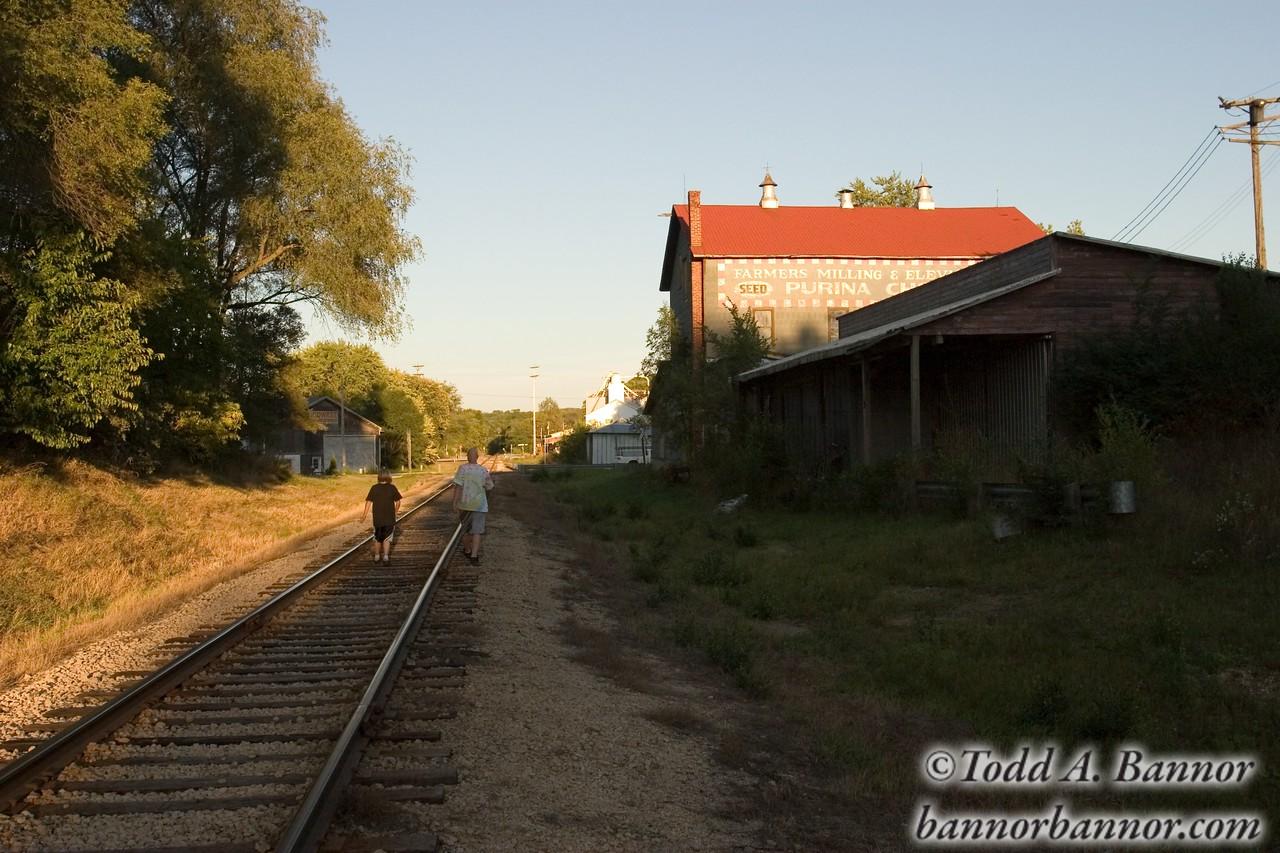 Two boys walking on railroad track. Palmyra, Wisconsin, USA.