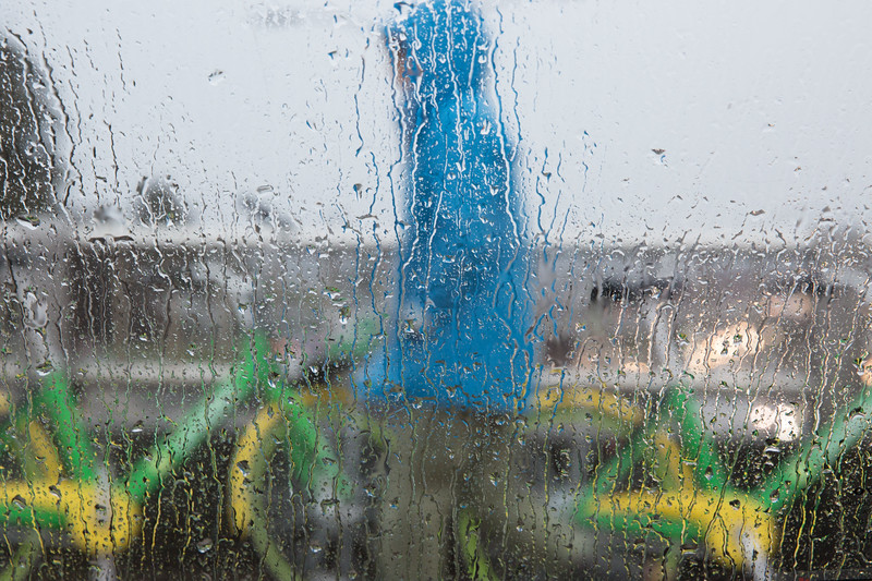 A bicycle commuter, seen through the rain covered window of a passing car, prepares to mount one of Seattle's over 9000 rental bikes. Three companies compete providing bikes that are unlocked  through a mobile app so riders can rent them for $1 per 30 minutes of usage. Soon electric assisted drive bikes will be available in hilly Seattle - at three times the price.