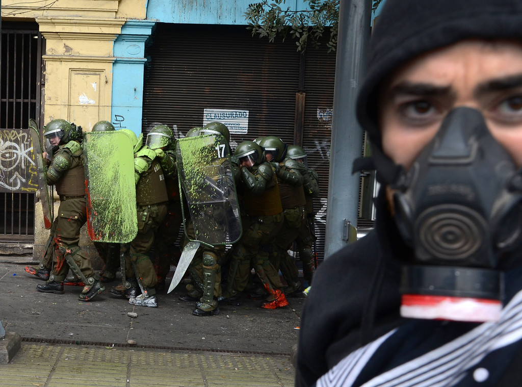 . Students clash with riot police during a protest to demand Chilean President Sebastian Pinera\'s government to improve the public education quality, in Santiago, on April 11,2013. PABLO TAPIA/AFP/Getty Images