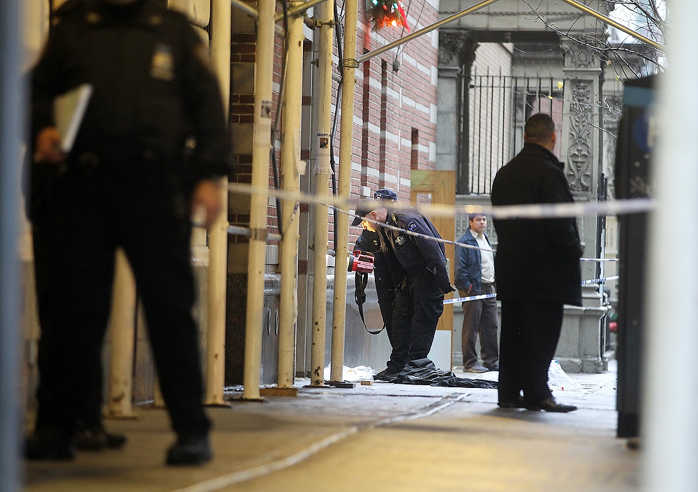 Description of . Police investigate the scene of a fatal shooting at 202 West 58th Street in Manhattan on December 10, 2012 in New York City.  The victim, identified as a male was shot in the head in broad daylight on the sidewalk and has since been pronounced dead.  (Photo by Mario Tama/Getty Images)