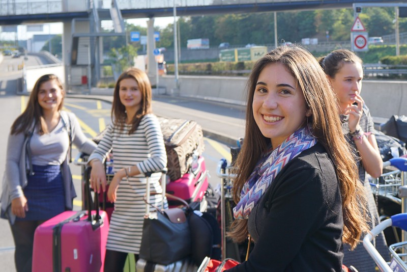 Abby, Laila, Claire, and Ellory outside the Geneva Airport getting ready to put their luggage on the bus