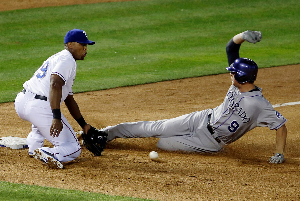 . Texas Rangers third baseman Adrian Beltre reaches out for the throw as Colorado Rockies\' D.J. LeMahieu (9) beats it out for a triple in the fifth inning of a baseball game, Wednesday, May 7, 2014, in Arlington, Texas. The hit came off of Rangers relief pitcher Scott Baker. (AP Photo/Tony Gutierrez)