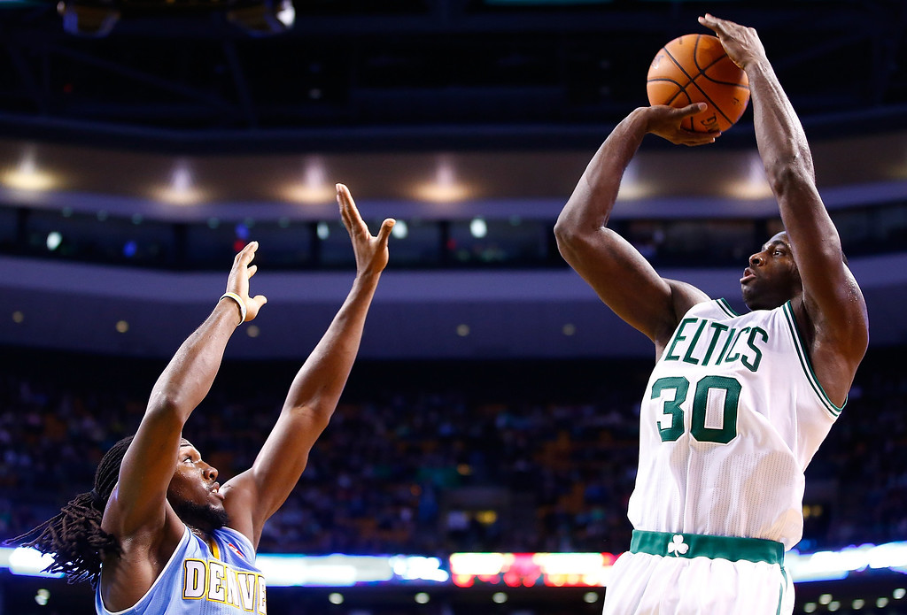 . BOSTON, MA - DECEMBER 06: Brandon Bass #30 of the Boston Celtics takes a shot over Kenneth Faried #35 of the Denver Nuggets in the second quarter during the game at TD Garden on December 6, 2013 in Boston, Massachusetts.  (Photo by Jared Wickerham/Getty Images)