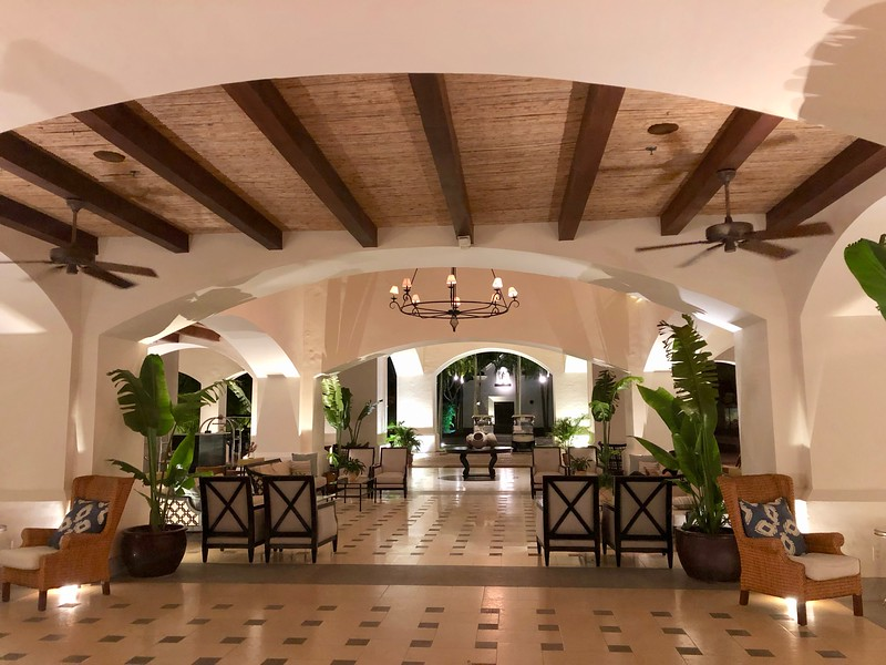 Hotel lobby with tile floors, arched ceilings in mission-style architecture.