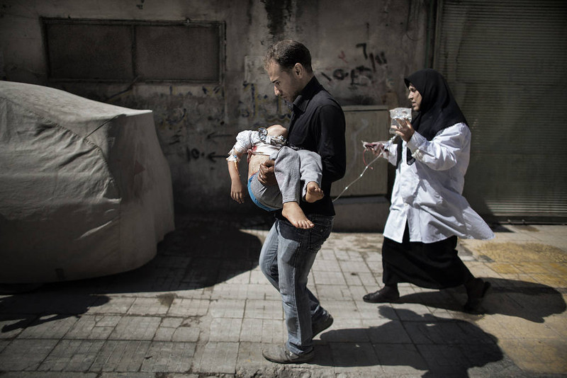 . A Syrian man carries his wounded daughter outside a hospital in the northern city of Aleppo on September 18, 2012. Syrian troops shelled several districts in Aleppo and clashed with rebels, as Damascus ally Iran proposed a simultaneous halt to the violence and a peaceful solution to the conflict. AFP PHOTO/MARCO LONGARI/AFP/Getty Images