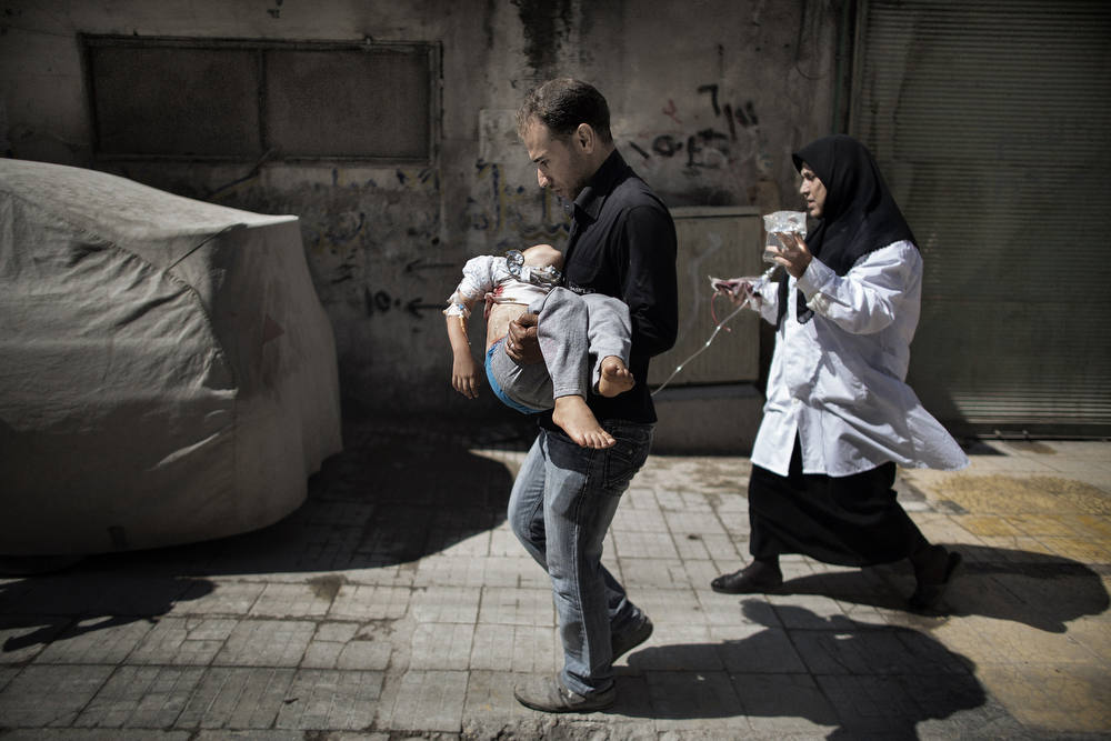 Description of . A Syrian man carries his wounded daughter outside a hospital in the northern city of Aleppo on September 18, 2012. Syrian troops shelled several districts in Aleppo and clashed with rebels, as Damascus ally Iran proposed a simultaneous halt to the violence and a peaceful solution to the conflict. AFP PHOTO/MARCO LONGARI/AFP/Getty Images