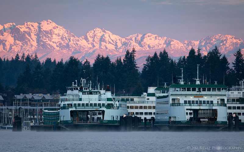 The morning sun lights up the Olympic Mountains, while it hasn't yet reached the ferries in Eagle Harbor on Bainbridge Island.