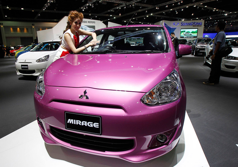 . A model poses beside a Mitsubishi Mirage during a media presentation of the 34th Bangkok International Motor Show in Bangkok March 26, 2013. The Bangkok International Motor Show will be held from March 27 to April 7. REUTERS/Chaiwat Subprasom