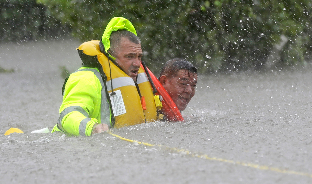 . Wilford Martinez, right, is rescued from his flooded car by Harris County Sheriff\'s Department Richard Wagner along Interstate 610 in floodwaters from Tropical Storm Harvey on Sunday, Aug. 27, 2017, in Houston, Texas. (AP Photo/David J. Phillip)