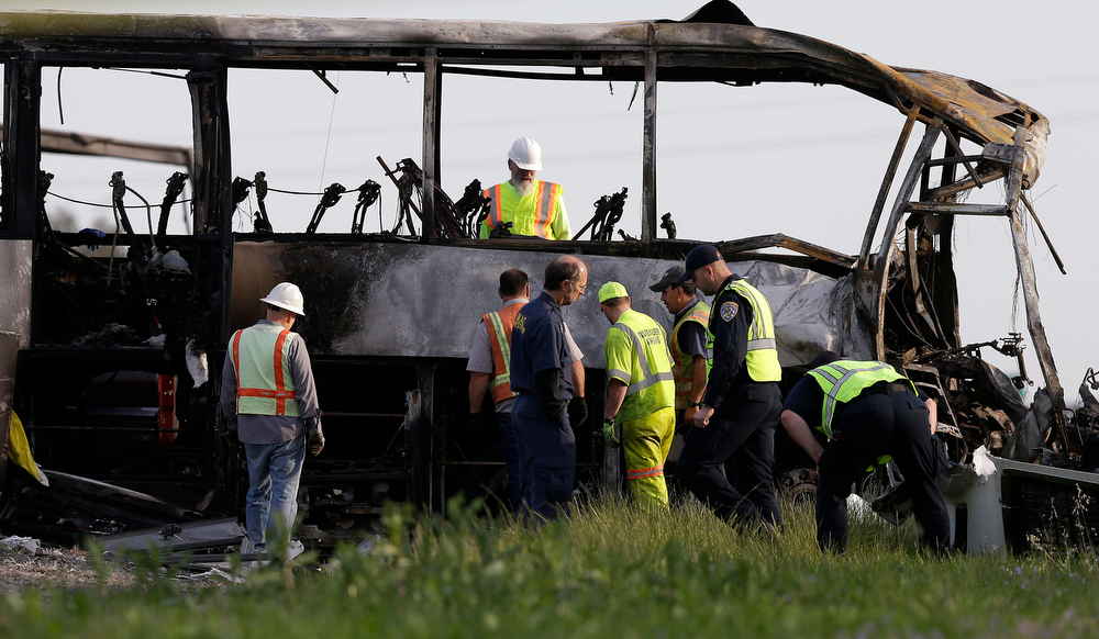 Description of . Officials and California Highway Patrol Officers look over the remains of a tour bus that was struck by a FedEx truck on Interstate 5 Thursday in Orland, Calif., Friday, April 11, 2014. At least ten people were killed and dozens injured in the fiery crash between the truck and a bus carrying high school students on a visit to a Northern California College. (AP Photo/Jeff Chiu)
