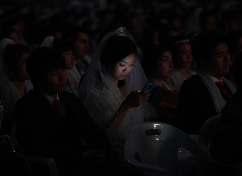 . A bride looks at her smartphone in a mass wedding ceremony at the CheongShim Peace World Center in Gapyeong, South Korea, Wednesday, Feb. 12, 2014. Some 2,500 South Korean and foreign couples exchanged or reaffirmed marriage vows in the Unification Church\'s mass wedding arranged by Hak Ja Han Moon, wife of the late Rev. Sun Myung Moon, the controversial founder of the Unification Church. (AP Photo/Lee Jin-man)