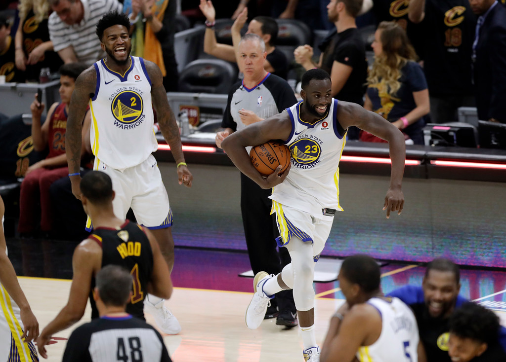 . Golden State Warriors\' Draymond Green (23) and Jordan Bell celebrate at the end of Game 4 of basketball\'s NBA Finals against the Cleveland Cavaliers, Friday, June 8, 2018, in Cleveland. The Warriors defeated the Cavaliers 108-85 and swept the series. (AP Photo/Tony Dejak)