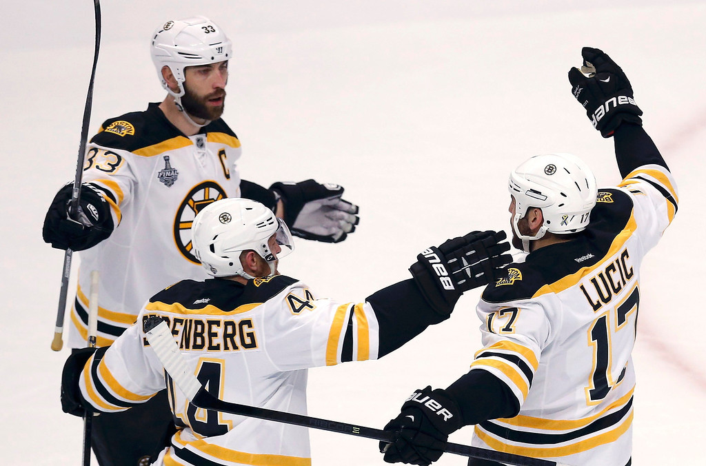 . Boston Bruins\' Milan Lucic (R) is congratulated by teammates Zdeno Chara (L) and Dennis Seidenberg after scoring on the Chicago Blackhawks during the first period in Game 1 of their NHL Stanley Cup Finals hockey game in Chicago, Illinois, June 12, 2013. REUTERS/Jim Young