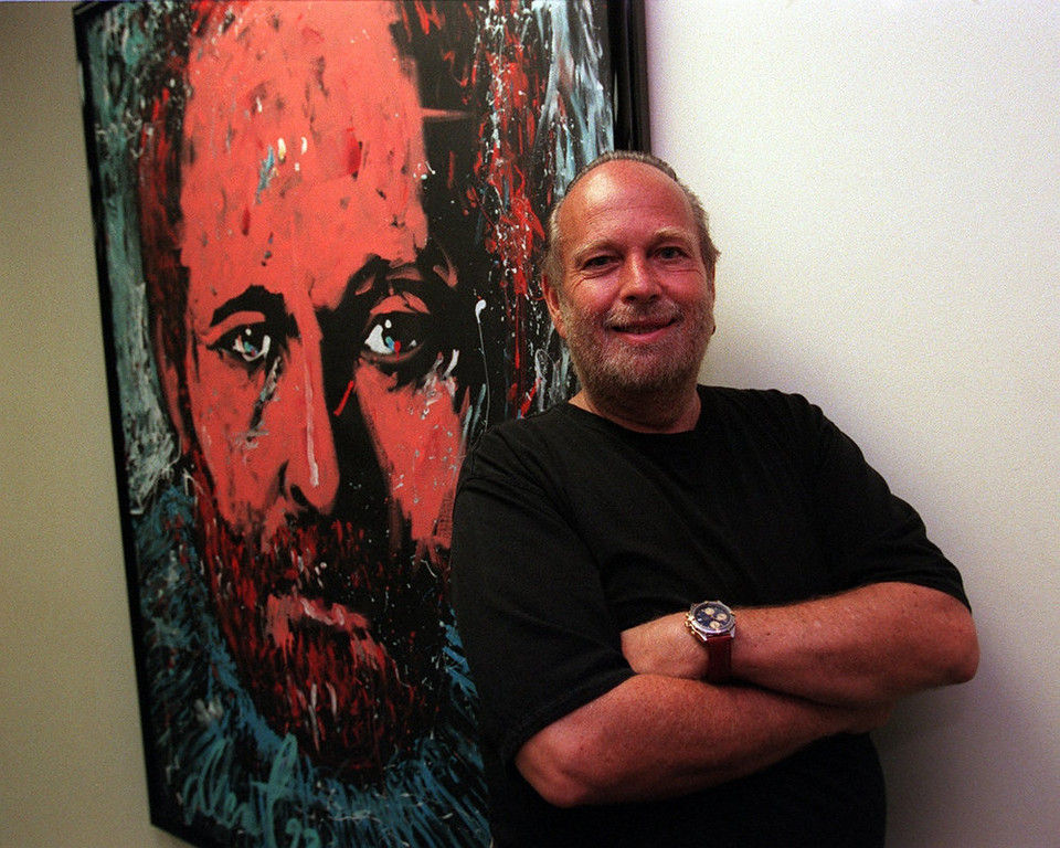 . Barry Fey, in his Greenwood Plaza Office, stands next to his own portrait done by artist Denny Dent.  Lyn Alweis/The Denver Post