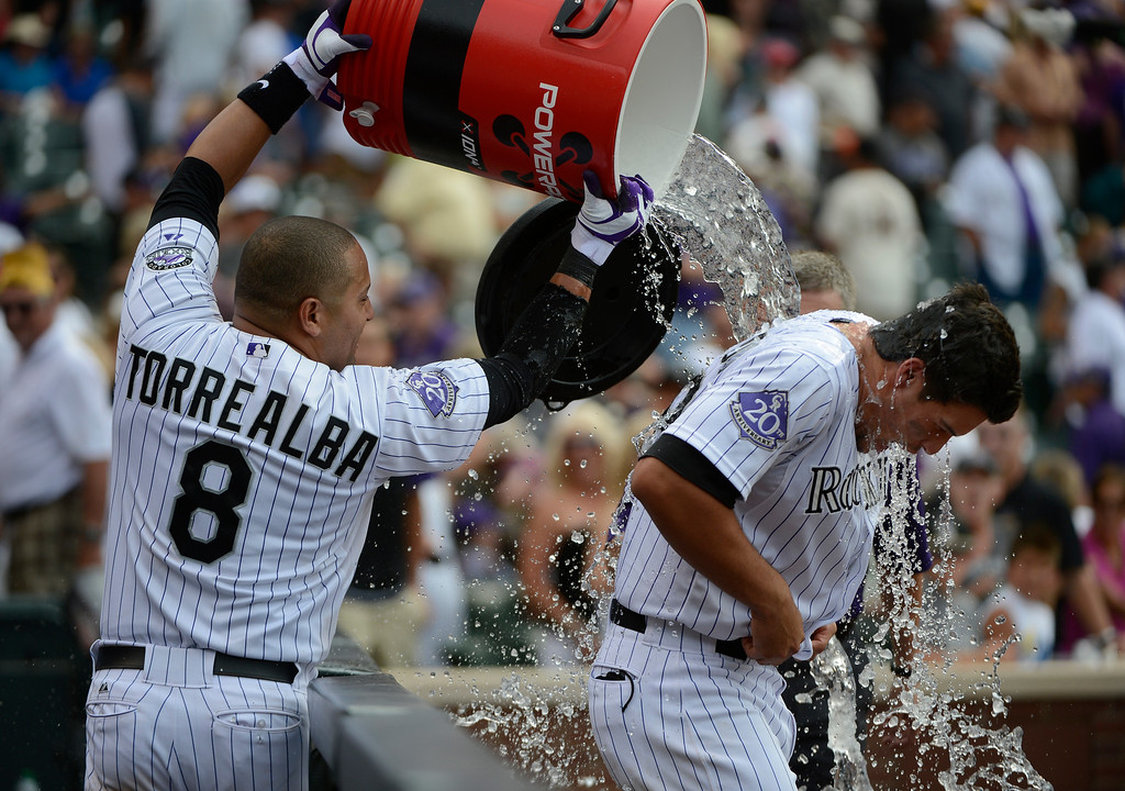 . DENVER, CO - JUNE 27: Colorado Rockies catcher, Yorvit Torrealba, douses third baseman, Nolan Arenado, celebrating Arenado\'s walk-off game winning single to defeat the San Francisco Giants 2-1 at Coors Field Saturday afternoon, June 29, 2013. (Photo By Andy Cross/The Denver Post)