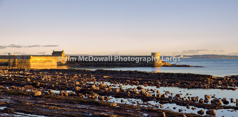 Sunset Reflecting off the harbour Walls of Old Saltcoats Pier on the Clyde in Scotland.