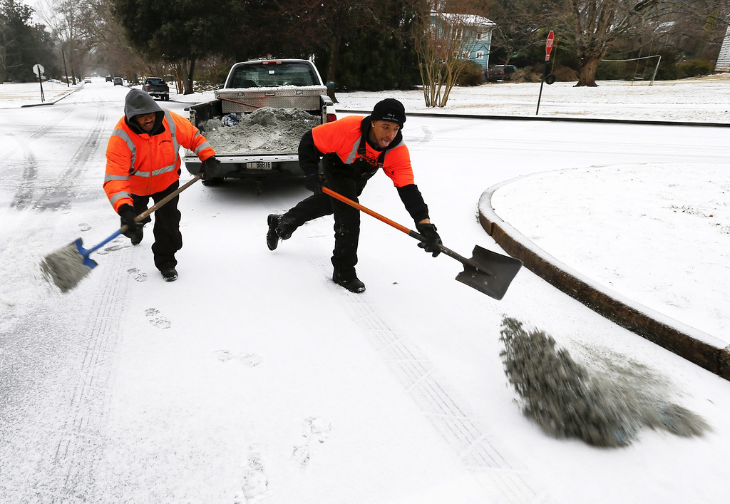 . City public works employees spread a mixture of sand and salt at a road intersection during a severe winter storm in Avondale Estates, Georgia, USA, 12 February 2014. Ice and snow in the metro Atlanta area and north Georgia is expected to make travel treacherous and cut electricity to thousands of customers.  EPA/ERIK S. LESSER