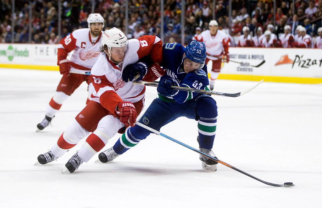 . Detroit Red Wings\' Justin Abdelkader, left, moves the puck with one hand on his stick while being checked by Vancouver Canucks\' Bo Horvat during the first period of an NHL hockey game in Vancouver, British Columbia on Saturday, Jan. 3, 2015. (AP Photo/The Canadian Press, Darryl Dyck)