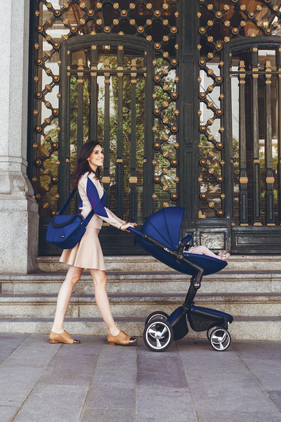 Mima_Xari_Lifestyle_Royal_Blue_Black_Chassis_Mum_Walking_With_Pushchair_Side_View.jpg
