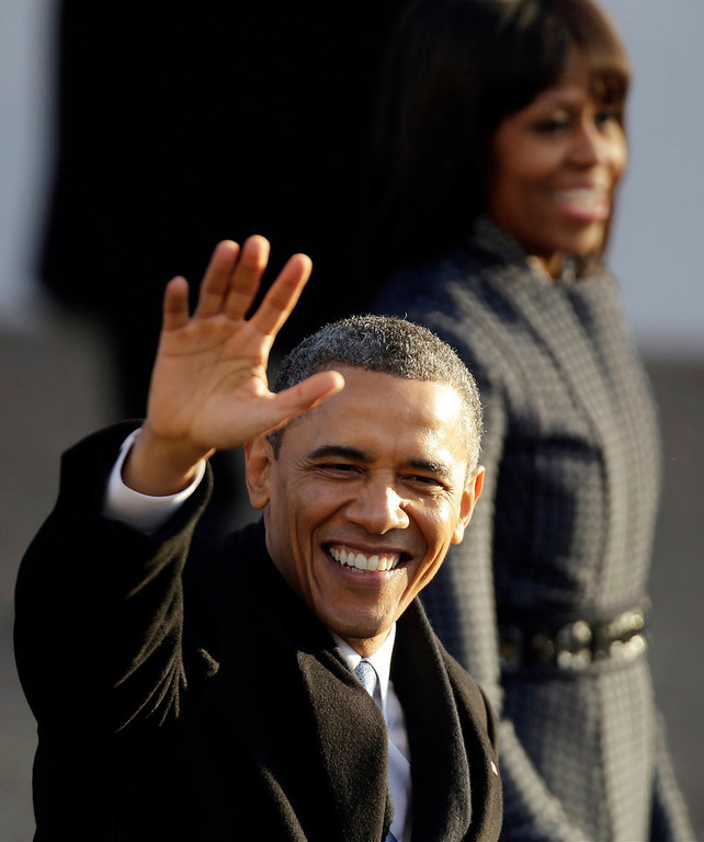 . President Barack Obama and first lady Michelle Obama walk the inaugural parade route walk down Pennsylvania Avenue en route to the White House, Monday, Jan. 21, 2013, in Washington. Thousands  marched during the 57th Presidential Inauguration parade after the ceremonial swearing-in of President Barack Obama. (AP Photo/Gerald Herbert)