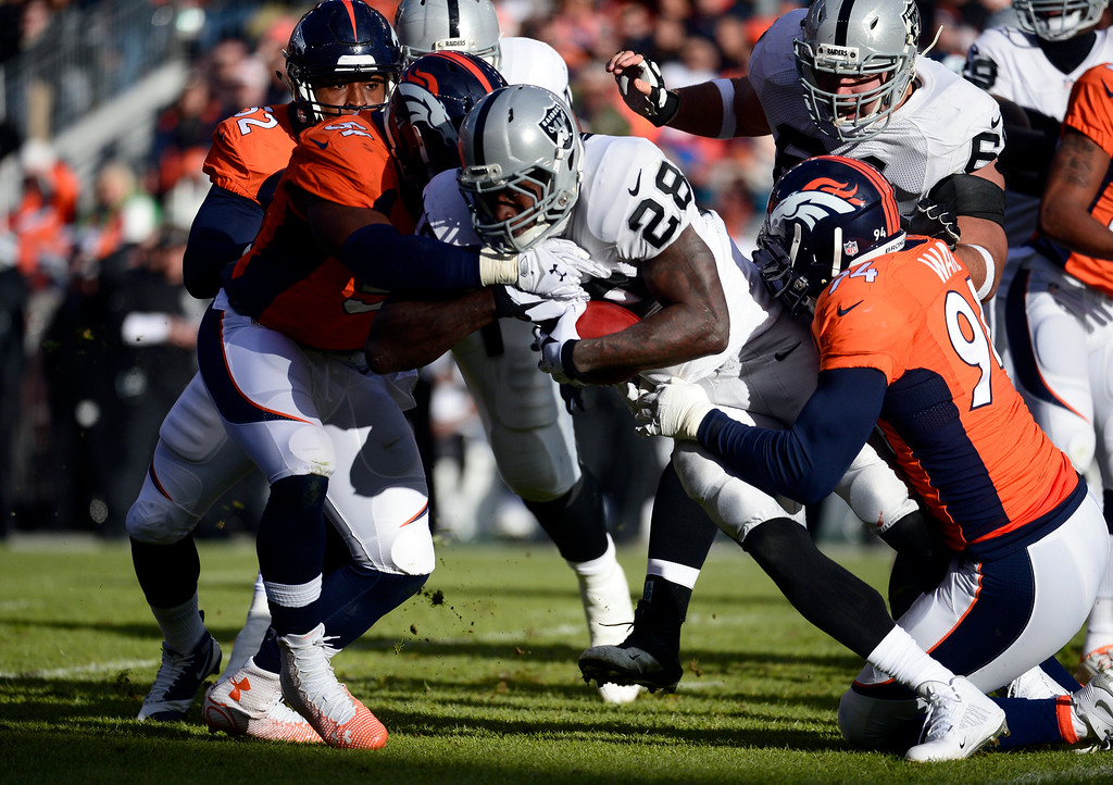 . DENVER, CO - DECEMBER 28: Latavius Murray (28) of the Oakland Raiders gets taken down by Todd Davis (51) of the Denver Broncos and DeMarcus Ware (94) of the Denver Broncos during the first quarter.  The Denver Broncos played the Oakland Raiders at Sports Authority Field at Mile High in Denver on December, 28 2014. (Photo by Tim Rasmussen/The Denver Post)