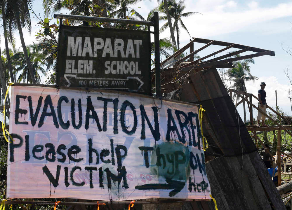 . A typhoon victim rebuilds his damaged house near a sign asking for aid for victims of Typhoon Bopha at Maparat township, Compostela Valley in southern Philippines Saturday Dec. 8, 2012. Search and rescue operations following typhoon Bopha that killed nearly 600 people in the southern Philippines have been hampered in part because many residents of this ravaged farming community are too stunned to assist recovery efforts, an official said Saturday.