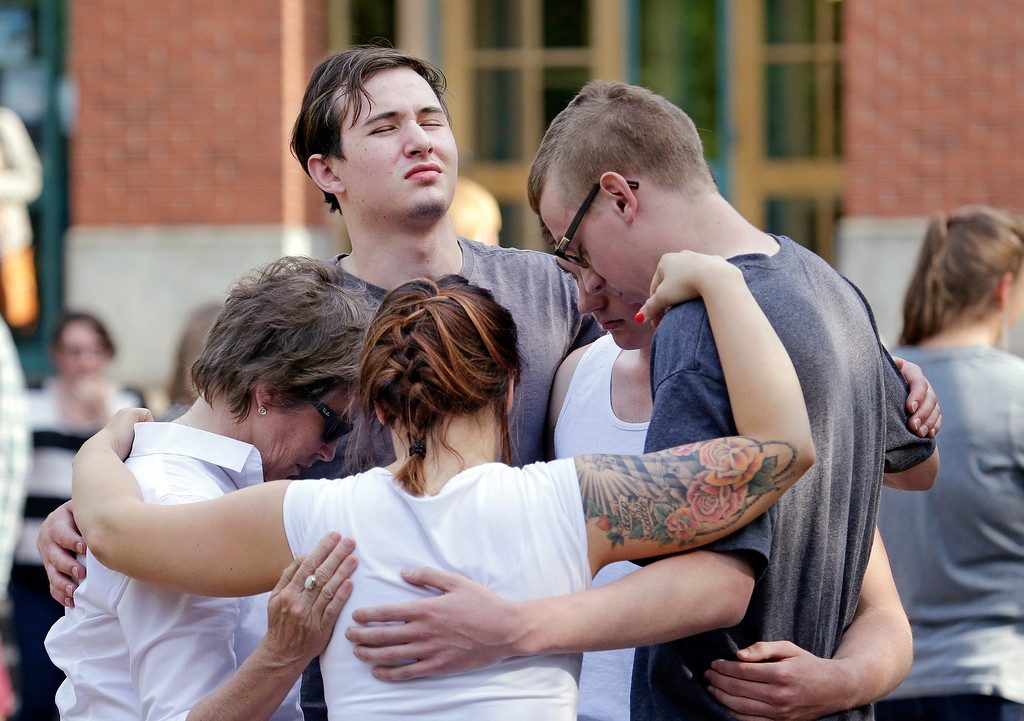 . Students and faculty pray together following a shooting on the campus of Seattle Pacific University Thursday, June 5, 2014, in Seattle. Seattle police now say there are four victims in a shooting and say one suspect is in custody. Police say one man and one woman have life-threatening injuries while another man and another woman are reported in stable condition.(AP Photo/Elaine Thompson)