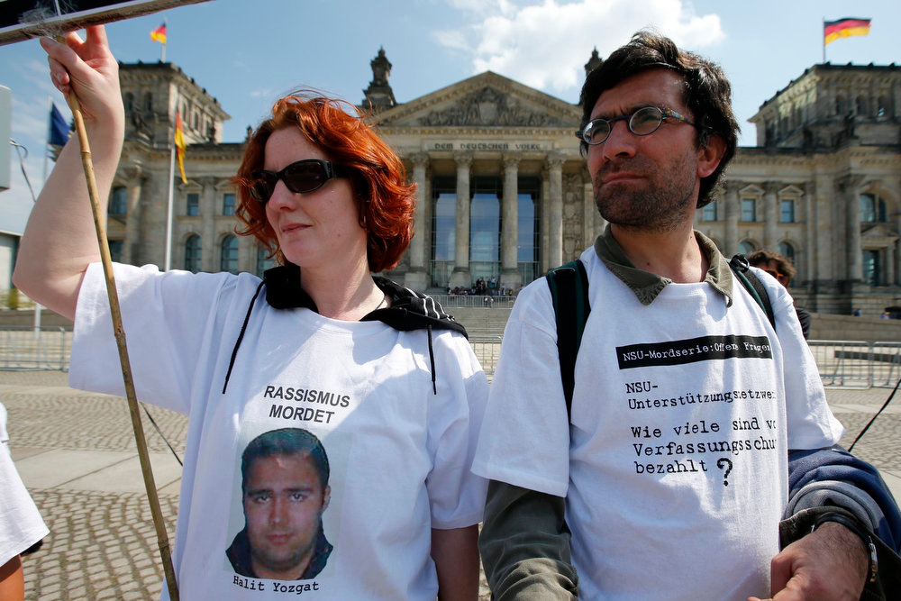 ". A protestor wearing a t-shirt with a picture of a victim (L) killed by the neo-Nazi group National Socialist Underground (NSU) takes part in a protest in front of the Reichstags building in Berlin on May 6, 2013. The surviving member of a German neo-Nazi cell went on trial on Monday for a series of racist murders that scandalized Germany and exposed authorities\' inability or reluctance to recognize right-wing hate crime. Words on t-shirt (R) read, ""NSU series of murders: pending questions. NSU - support network: How many are paid by the intelligence service\"". REUTERS/Fabrizio Bensch"