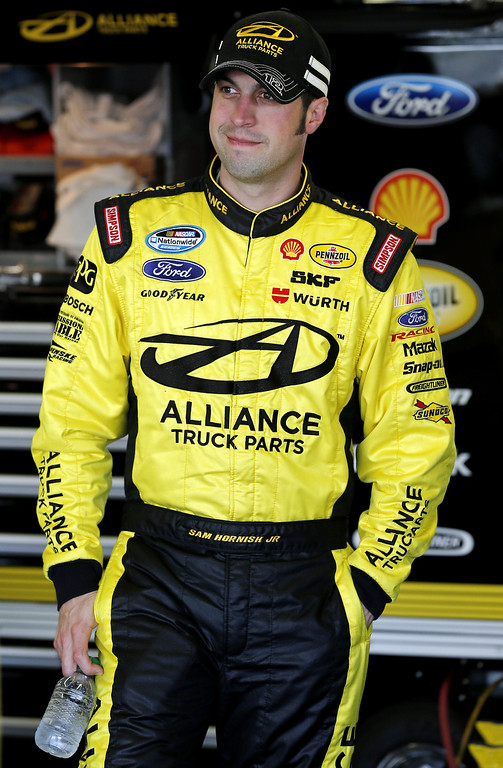 . Sam Hornish Jr., driver of the #12 Alliance Truck Parks Ford, stands by his car in the garage during practice for the NASCAR Nationwide Series DRIVE4COPD 300 at Daytona International Speedway on February 21, 2013 in Daytona Beach, Florida.  (Photo by Sam Greenwood/Getty Images)