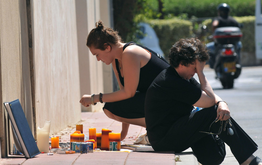 . An Israeli woman lights a candle while another one cries at the doorstep of late Israeli Air Force pilot Assaf Ramonís family house in Ramat Gan near Tel-Aviv, on September 14, 2009. Israel was in mourning following the death of the pilot son of the Jewish state\'s first and only astronaut, himself killed in the 2003 Columbia space shuttle disaster. Assaf Ramon, 21, died on September 13 when the F-16 fighter jet he was flying crashed in the southern hills of the occupied West Bank. YEHUDA RAIZNER/AFP/Getty Images