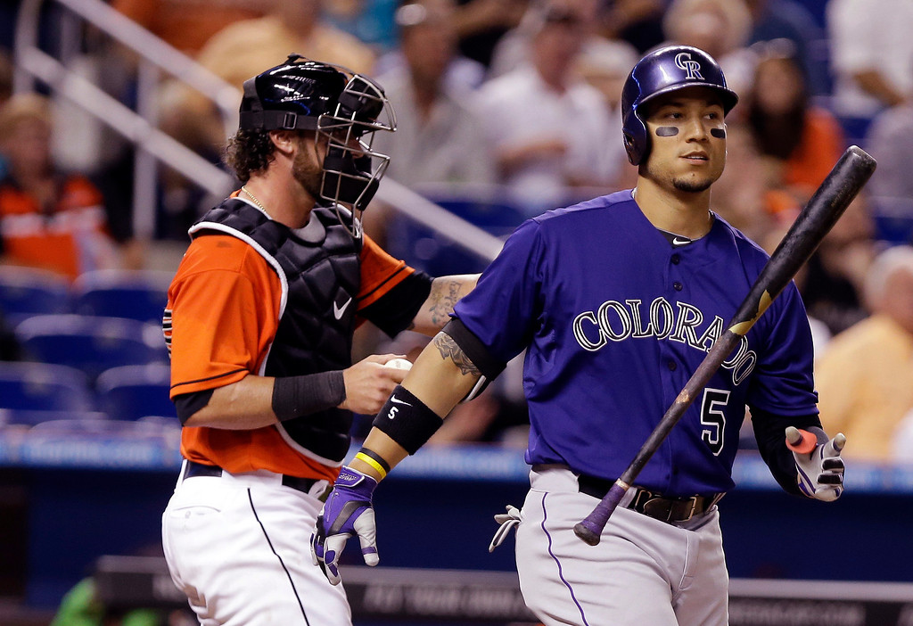 . Colorado Rockies\' Carlos Gonzalez (5) tosses his bat after striking out in the eighth inning during an opening day baseball game against the Miami Marlins, Monday, March 31, 2014, in Miami. At left is Miami Marlins catcher Jarrod Saltalamacchia. The Marlins defeated the Rockies 10-1. (AP Photo/Lynne Sladky)