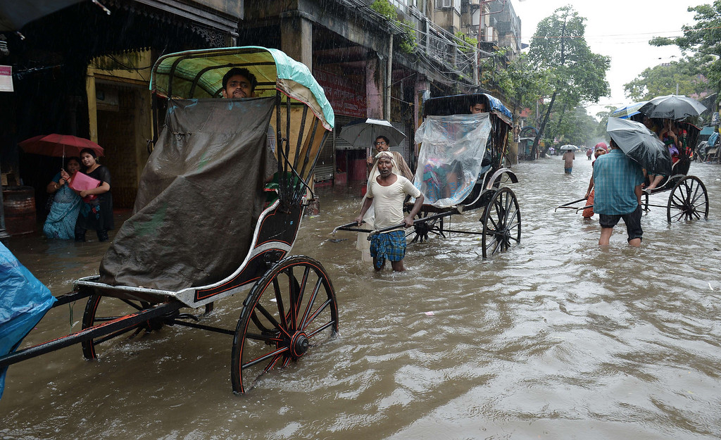 . Indian rickshaw pullers carry students through water-logged streets in Kolkata on October 26, 2013.  Persistent rain for the last 24 hours has thrown normal life out of gear with reports of water logging at major arterial roads of the city which received 14 cm rainfall, the highest rainfall during the ongoing depression in eastern India. DIBYANGSHU SARKAR/AFP/Getty Images
