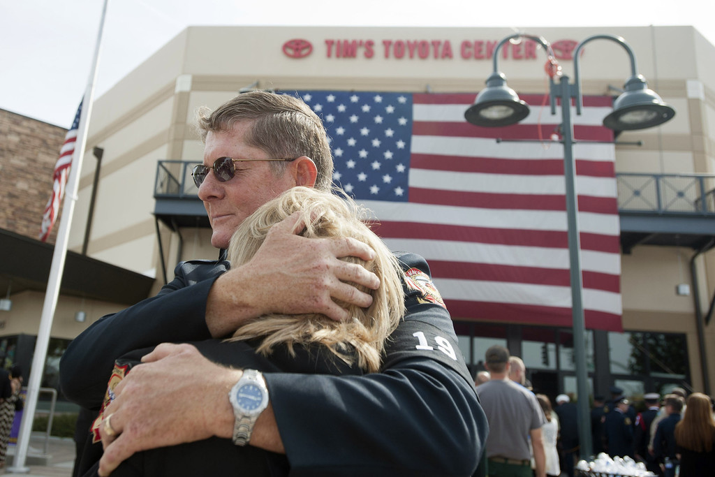 . Chaplain Bob Ossler with the Mayer, Arizona fire department hugs Mary Dalton, assistant chief of the Sun City West Fire Department, at the entrance to a memorial service honoring the 19 firefighters killed in a wildfire at Tim\'s Toyota Center July 9, 2013 in Prescott Valley, Arizona. (Photo by Laura Segall/Getty Images)