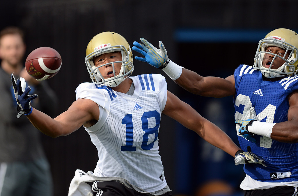 . UCLA receiver Thomas Duarte #18 keeps his eyes on the ball as Ishmael Adams #24 defends during football practice at Spaulding Field on the UCLA campus Thursday, April 17, 2014. (Photo by Hans Gutknecht/Los Angeles Daily News)